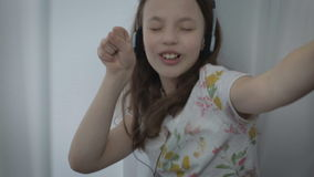 Beautiful little girl in headphones singing a song emotionally and dancing at window. stock footage