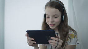 Beautiful little girl with headphones watching funny videos on tablet stock video footage