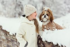 Beautiful little girl with her dog on the snow in winter royalty free stock image