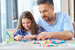 Beautiful little girl with her father playing with colored set for creativity.  Royalty Free Stock Image