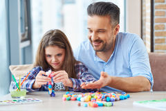 Beautiful little girl with her father playing with colored set for creativity.  Royalty Free Stock Photos