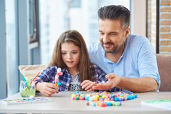 Beautiful little girl with her father playing with colored set for creativity.  Stock Photo