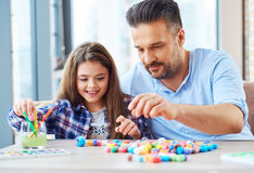 Beautiful little girl with her father playing with colored set for creativity.  Royalty Free Stock Photography