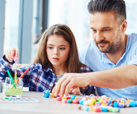 Beautiful little girl with her father playing with colored set for creativity.  Royalty Free Stock Images