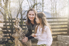 Beautiful little girl and her mom hugging animal ROE deer in the Stock Photos