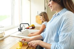 Beautiful little girl with the mother in the kitchen preparing a royalty free stock photography