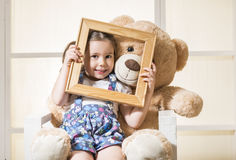 Beautiful little girl and her Teddy bear friend. Posing with an empty frame Royalty Free Stock Photography