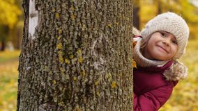 Beautiful little girl hiding behind tree in autumn. Childhood, season and people concept - beautiful little girl hiding behind tree in autumn stock footage