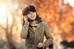 Beautiful little girl hold mobile phone and gladness talk. Vertical photo, stylish beautiful little girl hold mobile phone and gladness talk Royalty Free Stock Images