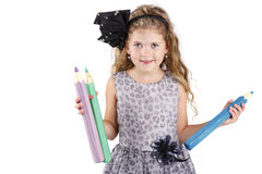 Beautiful little girl holding big crayons Stock Photos