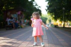 Beautiful little girl holding a big heart shaped lollipop. Royalty Free Stock Photo