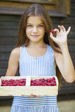 Beautiful little girl holding a box with a raspberry Royalty Free Stock Photos