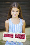Beautiful little girl holding a box with a raspberry Stock Photography