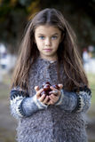 Beautiful little girl holding a chestnut Stock Photo