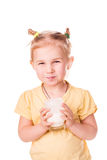 Beautiful little girl holding a glass of fresh milk. Stock Photos
