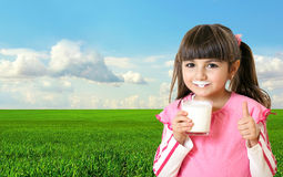Beautiful girl holding a glass of milk in the background of gree Royalty Free Stock Photography