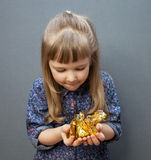Beautiful little girl holding handful with sweets. Grey background Royalty Free Stock Photos