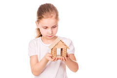 Beautiful little girl holding a toy model house. Buying a house concept. Royalty Free Stock Image