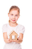 Beautiful little girl holding a toy model house. Buying a house concept. Stock Images