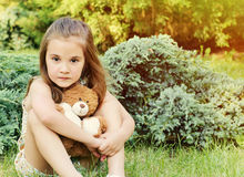 Beautiful little girl holding toy and sitting outdoors on the gr Royalty Free Stock Image