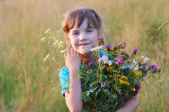 Beautiful little girl holds flowers and smiles in dry field Stock Photo