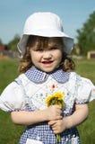 Beautiful little girl holds yellow dandelions Stock Photos