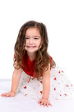Beautiful little girl in holiday dress. Happy and beautiful child wearing a red and white holiday dress Stock Images