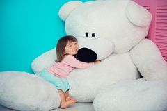Beautiful little girl hugging big white teddy bear. Royalty Free Stock Image