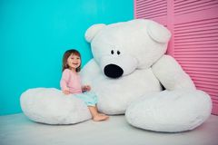 Beautiful little girl hugging big white teddy bear. Beautiful little girl hugging big white teddy bear royalty free stock photography