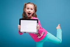 Beautiful Little Girl In Pink Shirt With Monkey And Blue Trousers Hold Empty Tablet Stock Photography