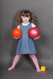 Beautiful little girl in jeans dress holds balls Stock Images