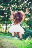 Beautiful little girl Is jumping outside at summer sunset royalty free stock photo