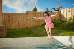 Beautiful little girl jumping into swimming pool Royalty Free Stock Photo