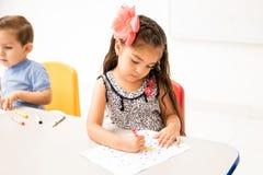 Kindergarten student coloring in class Stock Image