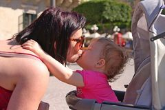 A beautiful little girl kisses her mommy. She seats in her push chair and tries to reach mom stock images