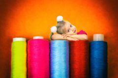 A beautiful little girl laid her head on the spools with thread for sewing. royalty free stock photos