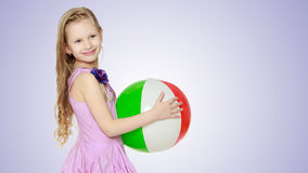 Beautiful little girl with a large multi-colored inflatable ball Royalty Free Stock Photos