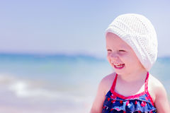 Beautiful little girl laughs on the background of the sea. Beautiful little girl laughs on the background of the sea on the beach. Selective focus stock photography