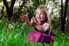 Beautiful little girl on a lawn with dandelions Royalty Free Stock Photos