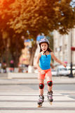 Beautiful little girl learning to roller skate in the city-park in summer season. Cute sportive little girl dressed in the colorful sportwear, with helmet and Stock Photography