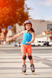 Beautiful little girl learning to roller skate in the city-park in summer season. Cute sportive little girl dressed in the colorful sportwear, with helmet and Royalty Free Stock Photo
