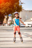 Beautiful little girl learning to roller skate in the city-park in summer season. Cute sportive little girl dressed in the colorful sportwear, with helmet and Royalty Free Stock Images