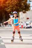 Beautiful little girl learning to roller skate in the city-park in summer season. Cute sportive little girl dressed in the colorful sportwear, with helmet and Stock Photo