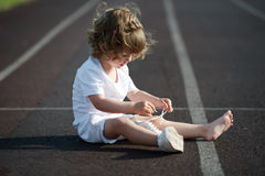 Beautiful little girl learning to tie shoelaces. Sweet beautiful little girl learning to tie shoelaces royalty free stock photography