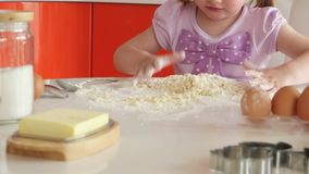 Beautiful little girl learns to cook in the kitchen stock video