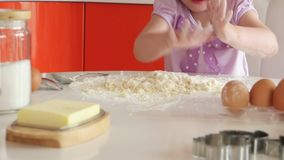Beautiful little girl learns to cook a meal in the kitchen stock footage