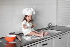 Beautiful little girl learns to cook a meal in the kitchen.  Stock Image
