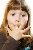 Beautiful little girl licking fingers Stock Photos