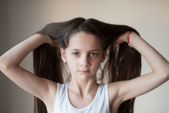 Beautiful little girl lifting up her hair by hands Stock Photography