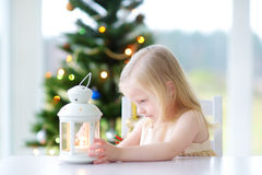 Beautiful little girl lighting a candle in white lantern Royalty Free Stock Photo
